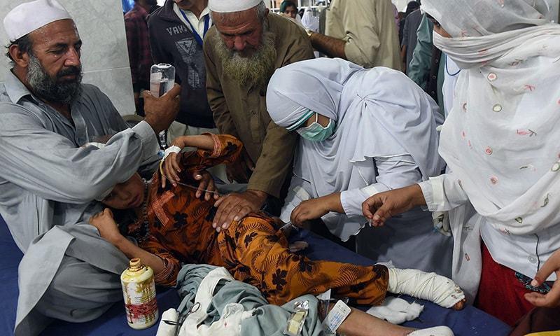 پشاور کے ایک ہسپتال میں طبی عملہ ایک زخمی بچی کو طبی امداد دے رہا ہے۔ 26 اکتوبر 2015. فوٹو اے ایف پی۔
