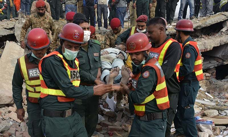Rescuers move a man rescued from under the rubble of the collapsed factory. —AFP