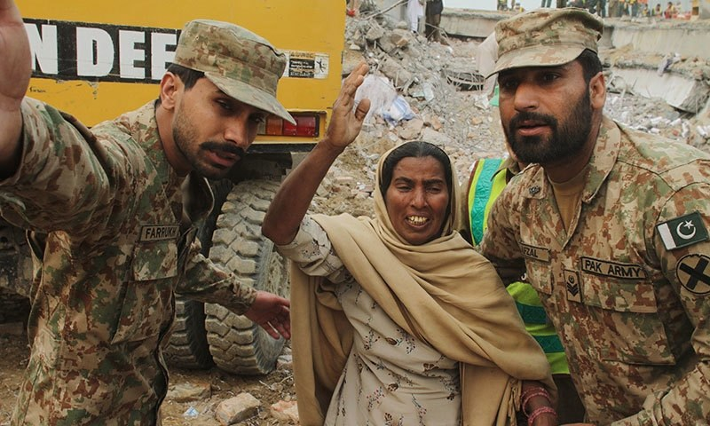 Pakistan army soldiers comfort a mother crying for her missing son,  Friday, Nov. 6, 2015. Hopes are starting to fade for finding more survivors in the rubble of a four-story factory which collapsed this week killings dozens of people left many injured.─AP