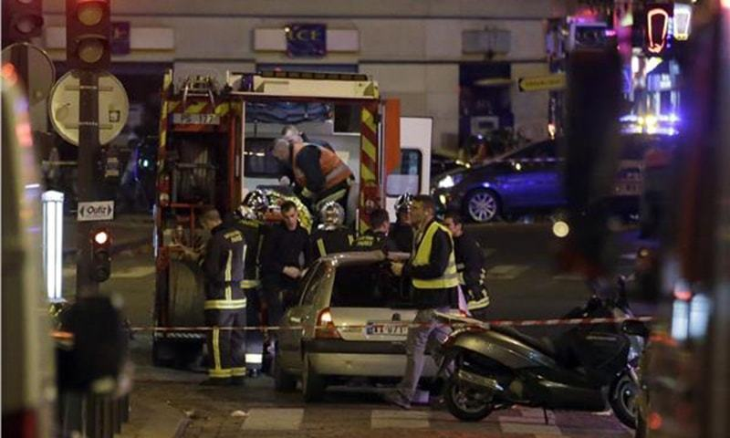 Ambulance workers are seen at the scene in the 10th arrondissement of the French capital Paris, following a string of attacks, on November 13, 2015.—AFP
