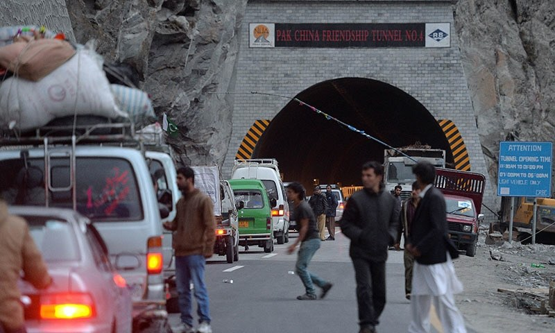 Tourists and passenger vehicles wait to travel through a newly built tunnel in northern Pakistan's Gojal Valley. — AFP