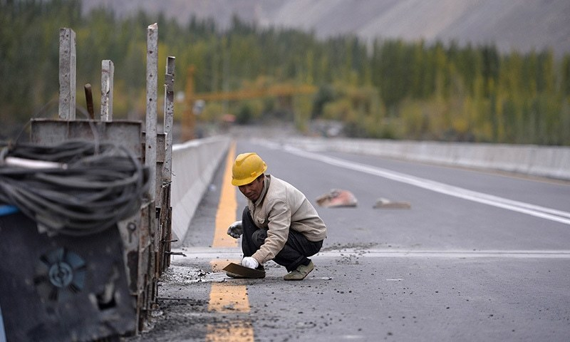 In this photograph taken on September 29, 2015, a Chinese labourer works on the Karakoram highway in Gulmit village of Hunza valley.  — AFP