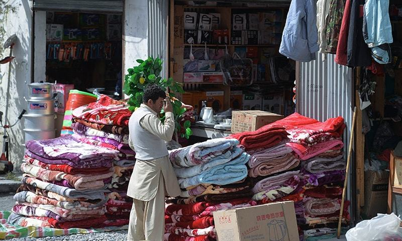 In this photograph taken on September 28, 2015, a shopkeeper arranges quilts outside his shop in the bazaar at Sost, the border town of Hunza valley in northern Pakistan.— AFP