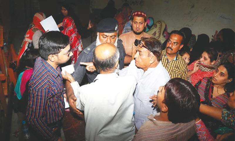 A POLICE officer intervenes to avert a clash between the presiding officer and a candidate at a Silawat Para polling station in Hyderabad on Thursday.—Online