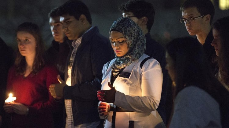 Director of Interfaith Engagement and Associate University Chaplain Tahera Ahmad holds a candle with other faculty and students at a vigil for the victims of the recent attacks in Paris, Beirut and Baghdad at Northwestern University. --Erin Hooley/Chicago Tribune