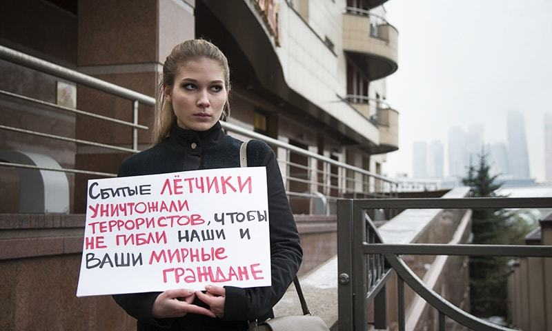 A woman holds a poster as she pickets the Turkish Embassy in Moscow, Russia, Tuesday, Nov. 24, 2015. —AP