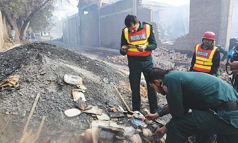 Rescue workers sift through the smouldering remains of the Pakistan Chipboard Factory in Jhelum. It was set ablaze by a mob on Nov 20 over blasphemy allegations.—Photo by writer