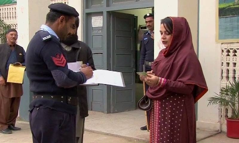 A voter confers with a policeman at a polling station. ─ DawnNews screengrab