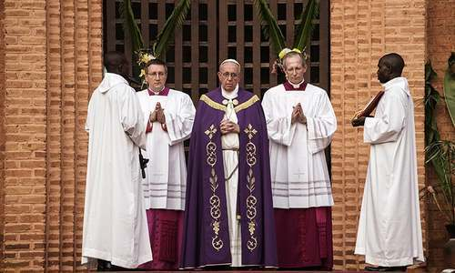"Pope Francis prays before the ""Holy Door"" at Bangui Cathedral in the Central African Republic. ─ AFP"