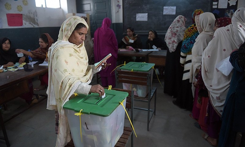 A voter casts her ballot at a polling station in Islamabad on November 30, 2015. — AFP
