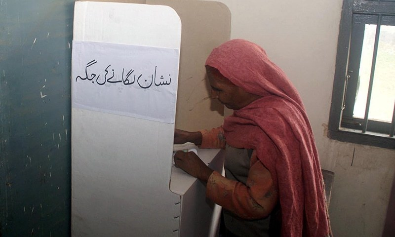A voter casts her ballot at a polling station. Islamabad is holding its first local government elections, amid tight security. — INP