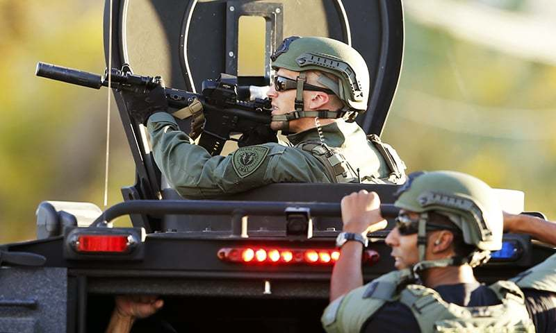 Police officers conduct a manhunt after a mass shooting in San Bernardino, California. -Reuters