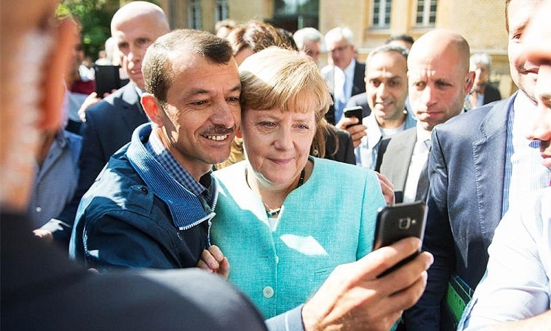 A migrant takes a selfie with German Chancellor Angela Merkel during a visit to a reception centre in Berlin. ─AFP/File