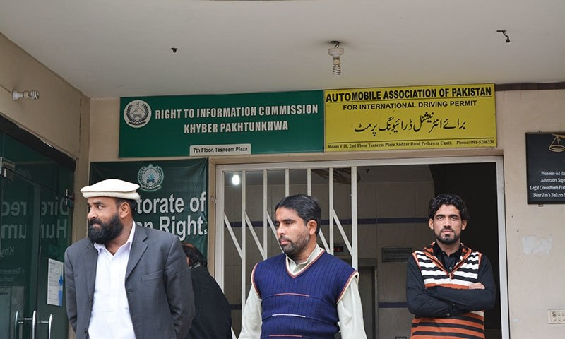 Men stand outside the RTIC office in Peshawar, KP. — Photo by author