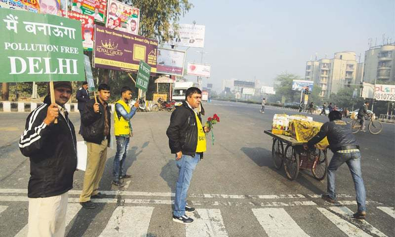 NEW DELHI: Holding flowers and placards, civil defence personnel try to raise awareness among motorists about the drive aimed at reducing pollution.—AP