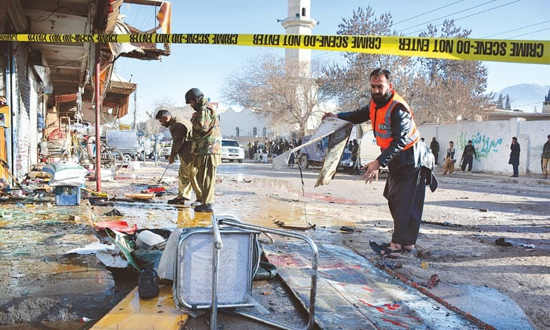 QUETTA: Security personnel examine the site of a suicide bombing here on Wednesday.—AP