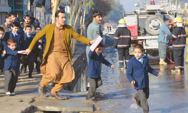 Jalalabad: An Afghan teacher, in brown, helps schoolchildren run from the site of clashes near the Pakistani consulate here on Wednesday. A number of Afghan security personnel were killed after gunmen attacked the Pakistani consulate.—AP