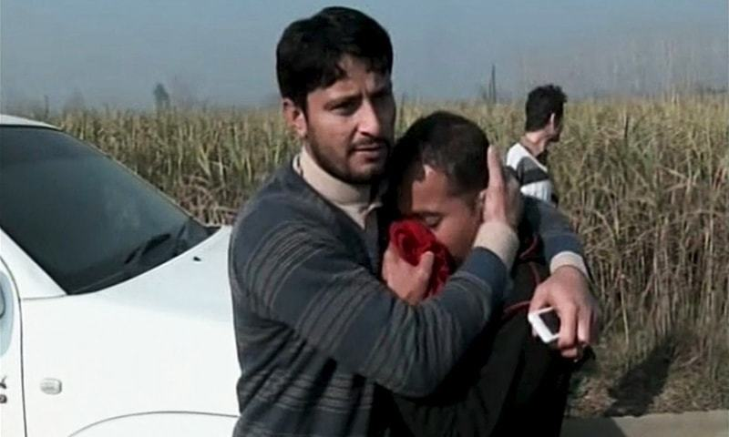 A man consoles a relative of a victim from the university attack — DawnNews