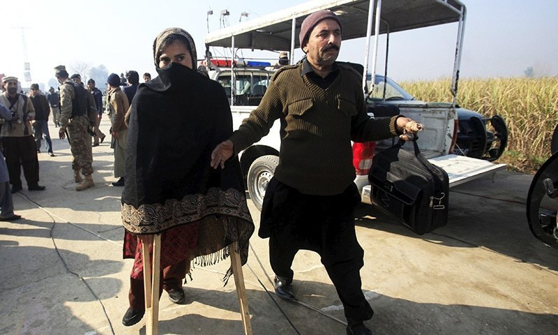 A teacher (L) walks with a pair of crutches following her rescue after a group of militants stormed the Bacha Khan University in Charsadda - Reuters