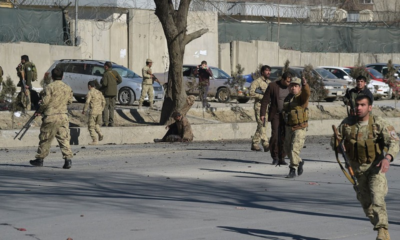 Afghan security personnel gather at the site of a suicide car bomb next to a police base in Kabul on February 1, 2016. — AFP