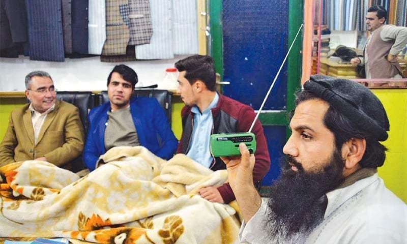 تصویر میں ایک افغان دکانداراپنی دکان پر شدت پسند تنظیم کی ریڈیو ٹرانسمیشن سن رہاہے—۔فائل فوٹو/ اے پی