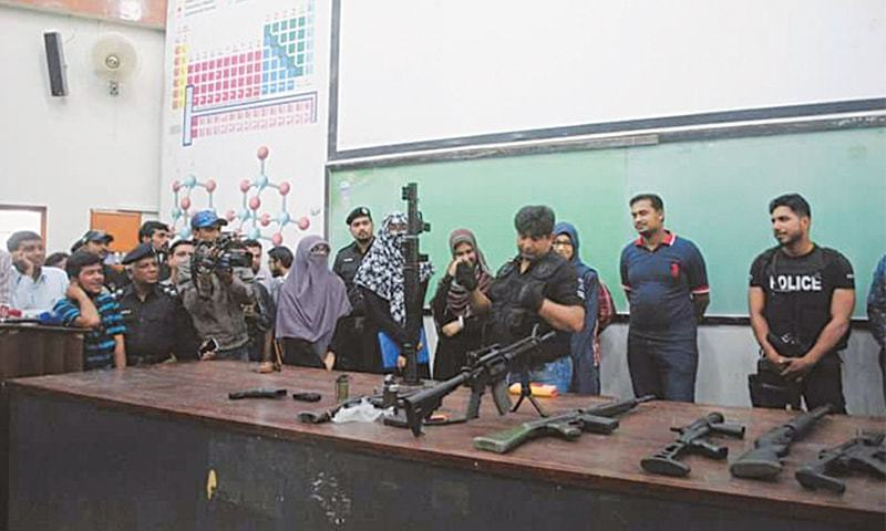 Students and teachers keenly look at the various weapons displayed by the Special Security Unit at Karachi University on Wednesday.