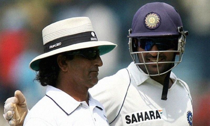 Indian cricketer Mahendra Singh Dhoni enjoys a light moment with umpire Asad Rauf during the final day of the first Test match between India and South Africa at The M.A. Chidambaram Stadium in Chennai on March 30, 2008. — AFP