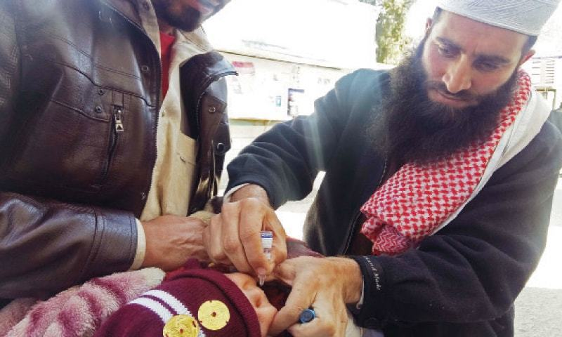 Mufti Samiullah, a local prayer leader, vaccinates a child in Saidu Sharif.—Dawn