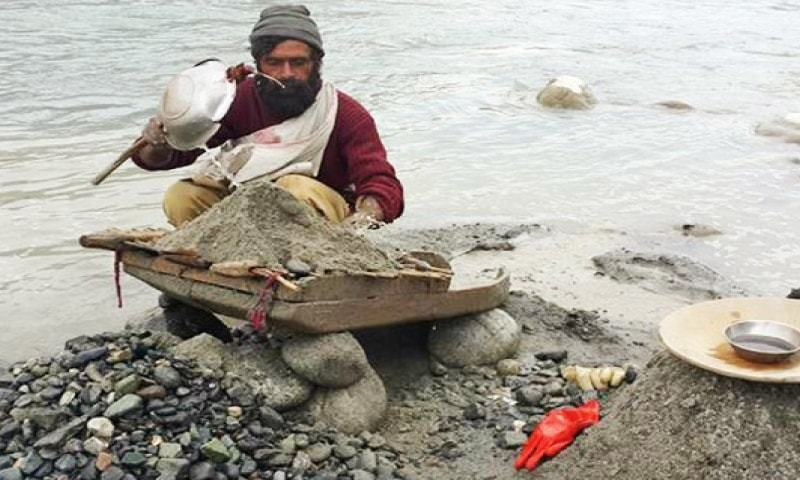 A man looks for gold wafers in the sand on the bank of Gilgit River.—Dawn