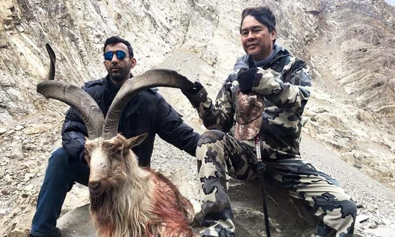 ایک غیر ملکی شکاری ہراموش، گلگت میں شکار کیے گئے مارخور کے ساتھ۔ — فوٹو معراج عالم۔