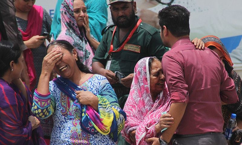 In this Wednesday, May 13, 2015 file photo, people mourn the deaths of their family members, gunned down on a bus in what was the Islamic State group's first appearance in Pakistan. ─AP