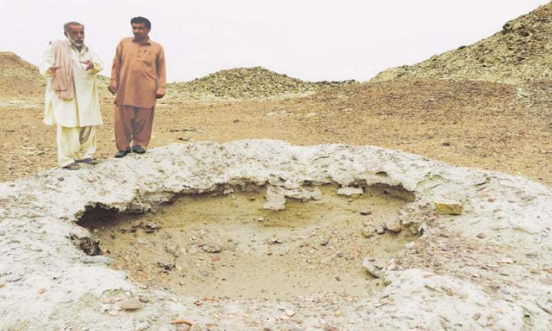 GWADAR: The 5000-year old site at Sutkagen Dor has seen a number of illegal excavations over the years. In this picture, Mohammad Rahim and former nazim Abdul Aziz stand above a portion dug up by illegal excavators who came looking for gold in Nov 2015.—Photo by writer