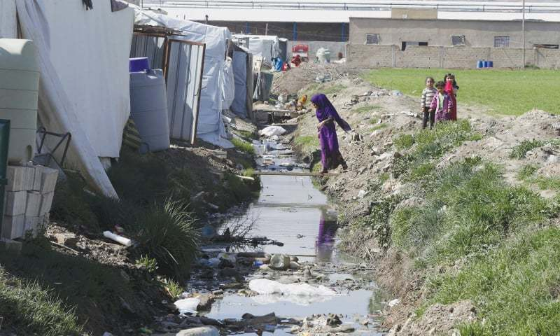 TIRBOL (Lebanon): A Syrian refugee girl walks on a wooden plank over sewage water inside an informal Syrian refugee camp here on Thursday. ─ Reuters