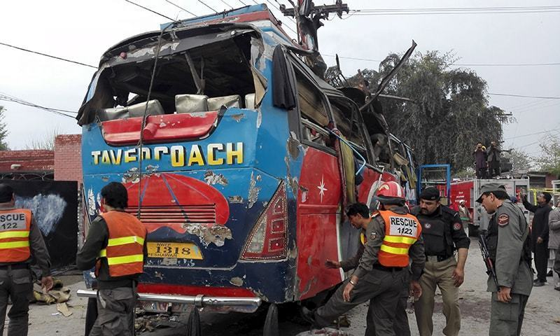 Security officials search the damaged bus after a bomb blast in Peshawar. ─ Reuters