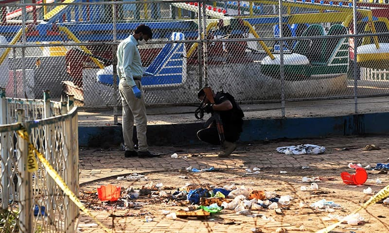 Security officials collect evidence at the cordoned-off site of the March 27 suicide bombing. ─ AFP
