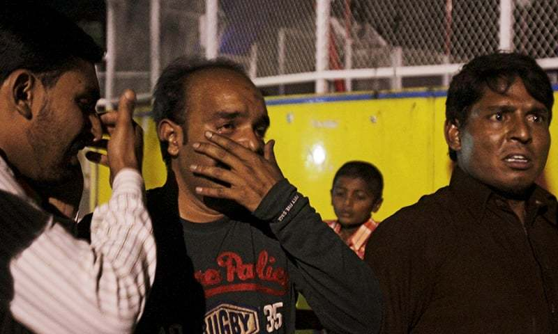 Men mourn the death of their relatives after a blast outside a public park in Lahore. — Reuters