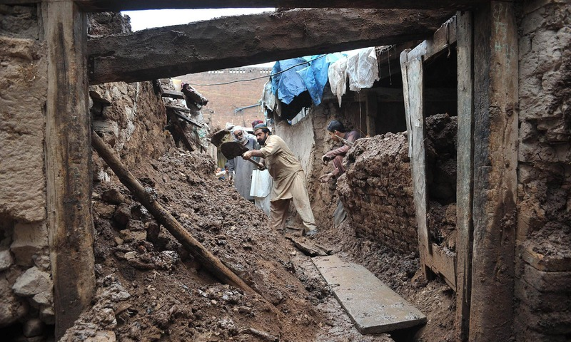 Residents remove debris from a damaged house after heavy rains in Peshawar. —AFP