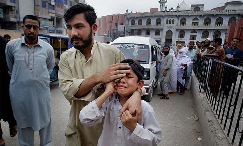 A man helps an injured boy to a hospital after an earthquake hit Peshawar, Pakistan. Photo: AP