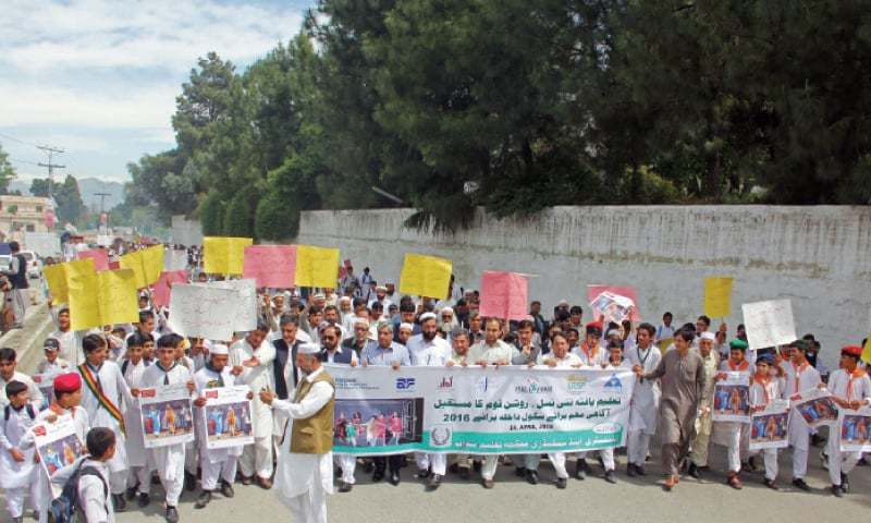 Students, teachers and civil society members stage an awareness walk to kick-off enrolment campaign in Mingora on Thursday. — Dawn