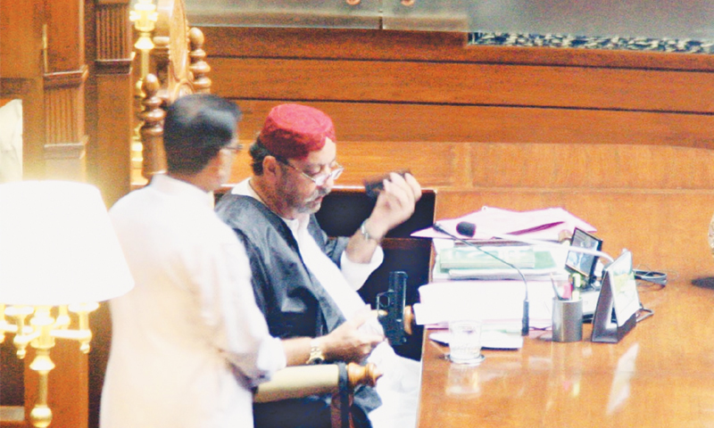 KARACHI: Sindh Assembly Speaker Agha Siraj Durrani examines the pistol brought inside the assembly by a TV crew.—Online