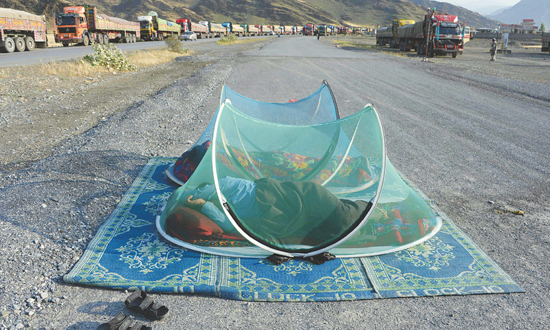 AFGHAN civilians sleep along a road near the Torkham border in Nangarhar province on Thursday. Hundreds of Afghans attempting to enter Pakistan, some for medical treatment, have been waiting in the open since the border was closed on May 9.—AFP