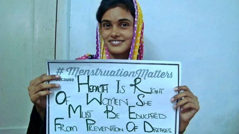 A girl holds up a #MenstruationMatters placard - Photograph courtesy WASH United