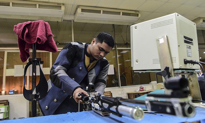 Bangladeshi shooter Abdullah Hel Baki preparing for his practice at a shooting complex in Dhaka. — AFP