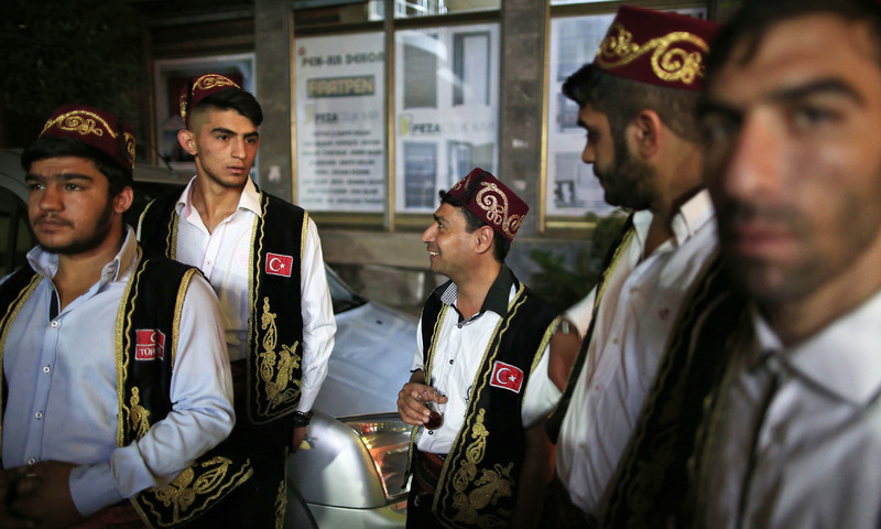 Drummers wearing traditional Ottoman clothes chat before performing on the streets of different neighbourhoods in Istanbul. —AP