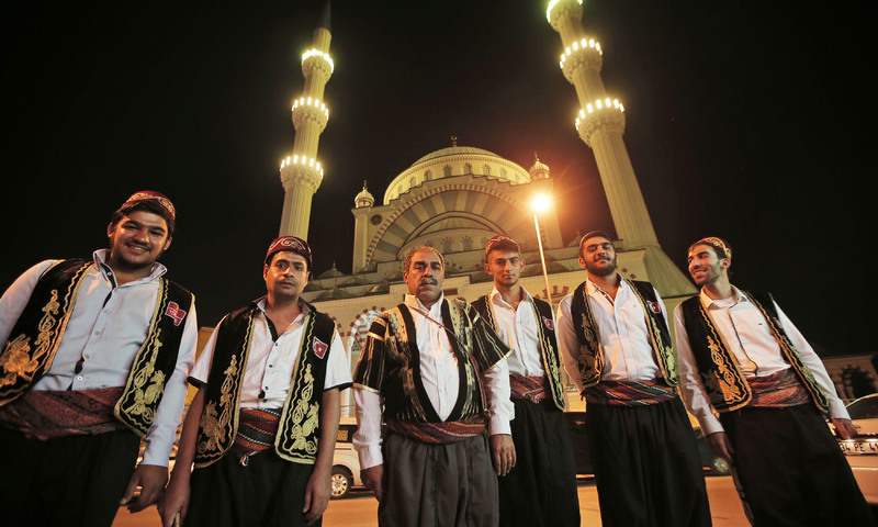 Drummers, backdropped by a mosque, pose for a photo before walking the streets in Istanbul. —AP