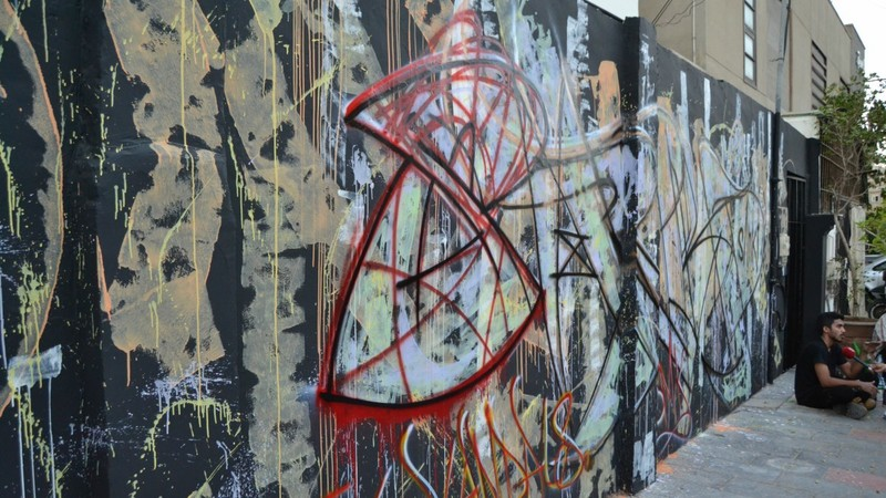 Live demonstration of graffiti on wall, plastic emulsion and acrylic on wall.