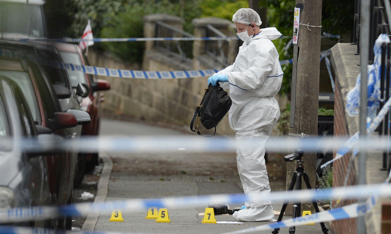 A forensic officer picks up a bag from the crime scene on the pavement outside the library in Birstall. —AFP