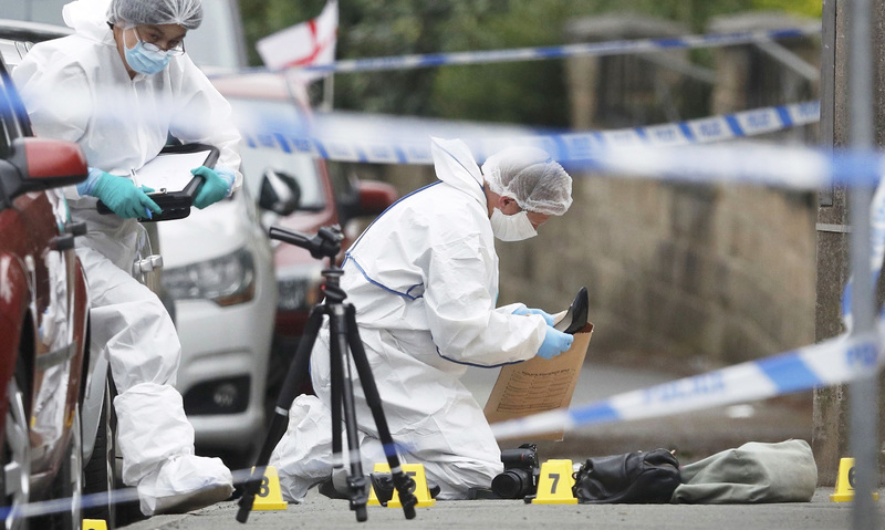 Forensics collect a woman's shoes on the ground behind a police cordon in Birstall. —Reuters