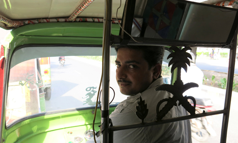 A rickshaw driver in Lahore. — Reuters