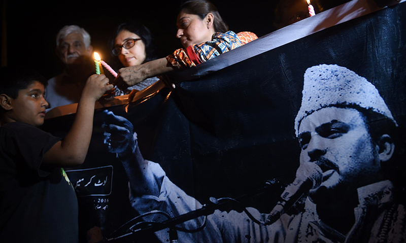 Activists light candles in Karachi, on June 23, 2016  in the memory of late Amjad Farid Sabri.— AFP